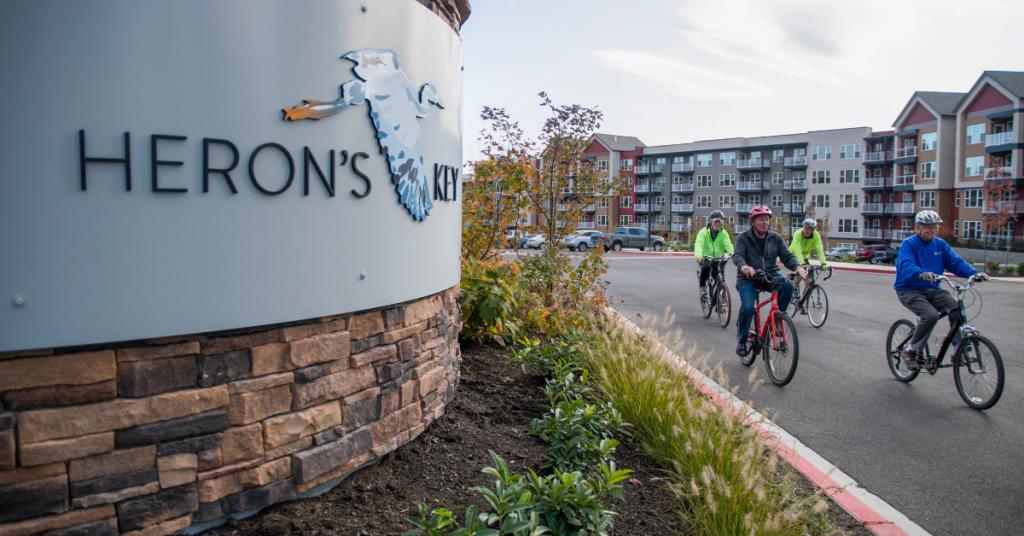 Seniors riding bikes outside by Heron's Key sign